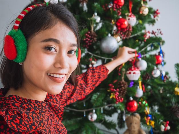 Chica asiática celebrando la navidad en casa, mujer decorar el árbol de navidad