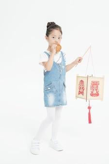 Chica asiática comiendo pastel de luna y sosteniendo la linterna