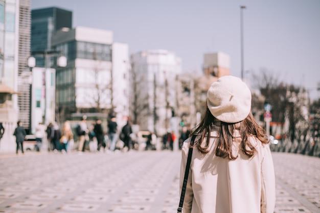 Chica asiática destacando entre la multitud en una calle de la ciudad en japón.