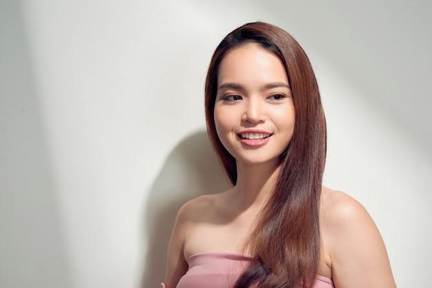 Chica asiática elegante con piel bronceada posando con expresión pensativa sobre fondo brillante.