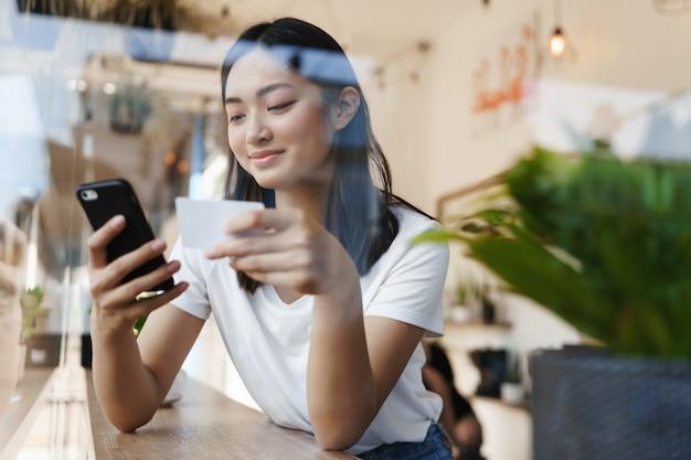 Chica asiática elegante sentada en un café cerca de la ventana, pagando compras en línea con tarjeta de crédito.