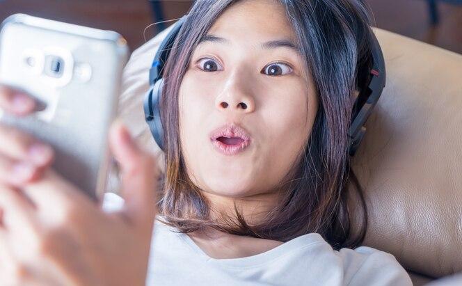 Chica asiática es sorprendentemente shock con contenido en su teléfono inteligente