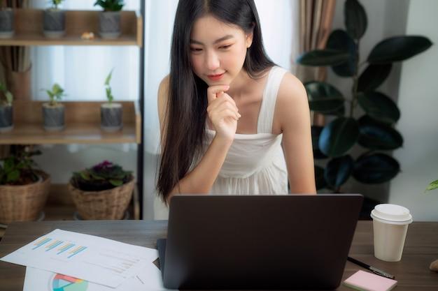 Chica asiática escribiendo datos en su computadora portátil para preparar su informe sobre la deak de madera