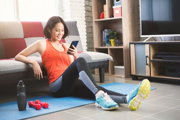 Chica asiática está escuchando la canción ejercicio en casa.