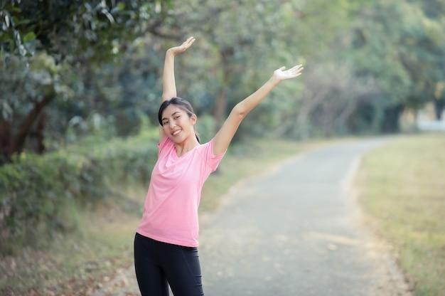 Chica asiática está estirando los músculos calientes de su cuerpo antes de salir a correr al parque