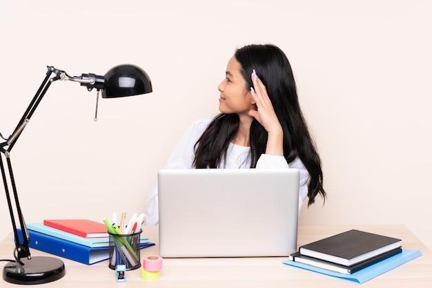 Chica asiática estudiante en un lugar de trabajo con una computadora portátil aislada en beige