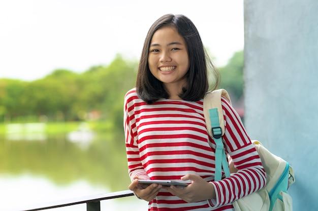 Chica asiática estudiante con una tableta digital en el parque en un día soleado de verano