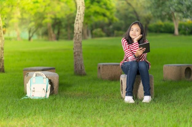 Chica asiática estudiante con una tableta digital en el parque de la escuela en un día soleado de verano