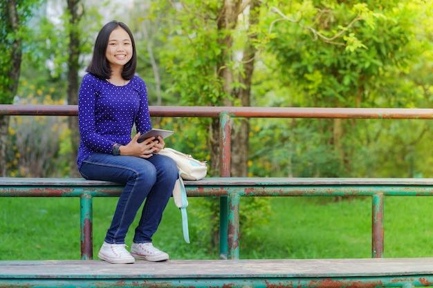 Chica asiática estudiante usando una tableta digital en el parque en un día soleado de verano