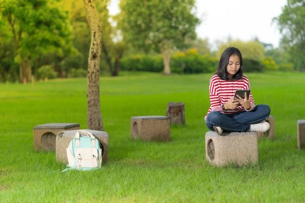 Chica asiática estudiante usando una tableta digital en el parque de la escuela en un día soleado de verano