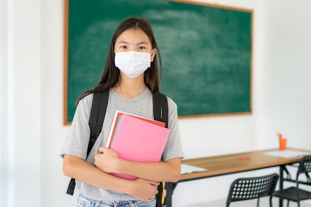 Chica asiática de estudiantes de primaria con mochila y libros con máscaras