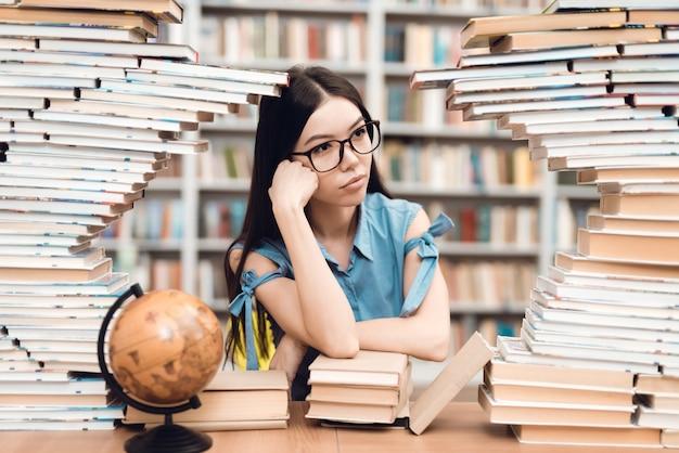 Chica asiática étnica sentado en la mesa rodeado de libros en la biblioteca.