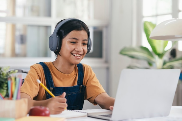 Chica asiática feliz aprendiendo en línea en casa