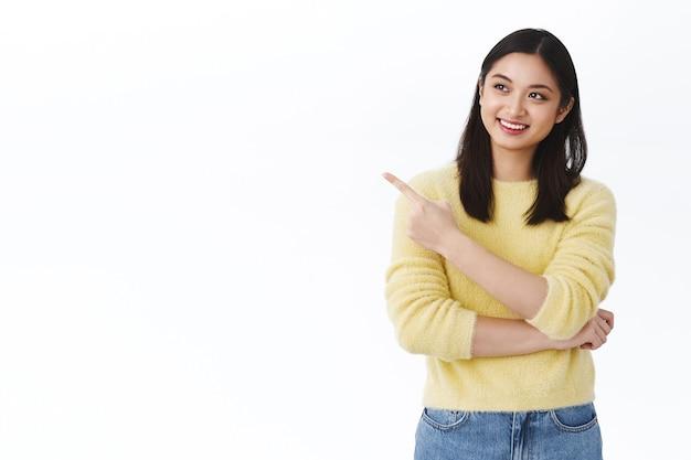 Chica asiática feliz soñadora con una sonrisa blanca radiante, apuntando con el dedo hacia la izquierda y mirando satisfecha con el anuncio, encontró una excelente opción, eligiendo el producto, tomando una decisión, pedido listo, pared blanca