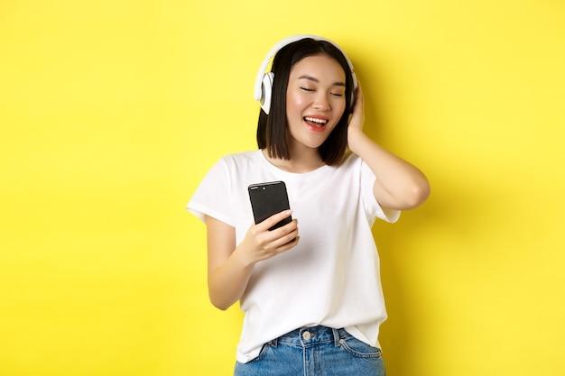 Chica asiática fresca cantando y escuchando música en auriculares inalámbricos, sosteniendo el teléfono inteligente en la mano, de pie sobre amarillo.