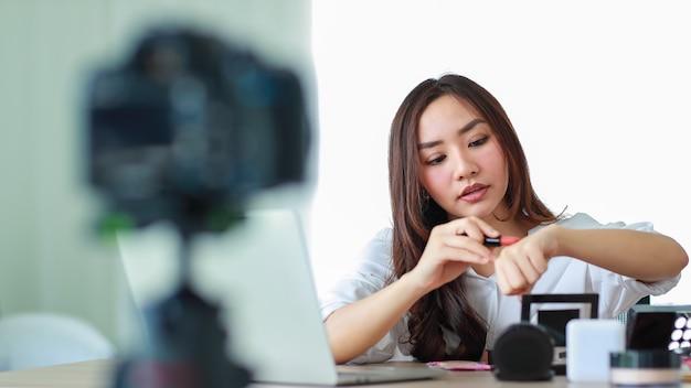 Chica asiática joven y hermosa que muestra el lápiz labial a la cámara y lo compara con el color de la piel durante la transmisión o grabación de video sobre revisión de cosméticos y blogger de belleza. concepto de marketing y venta online.