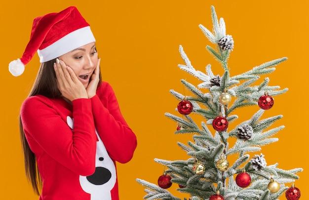 Chica asiática joven sorprendida con sombrero de navidad con suéter de pie cerca de árbol de navidad cubierto mejillas con manos aisladas sobre fondo naranja