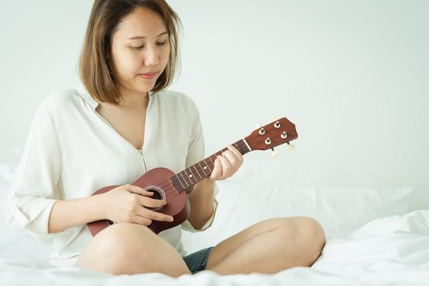 Chica asiática juega el ukelele