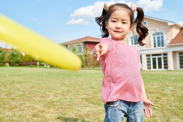Chica asiática jugando frisbee