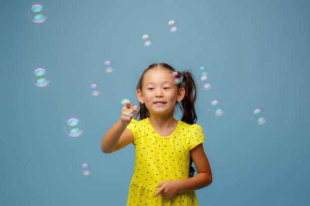 Chica asiática jugando con pompas de jabón en el estudio sobre un azul