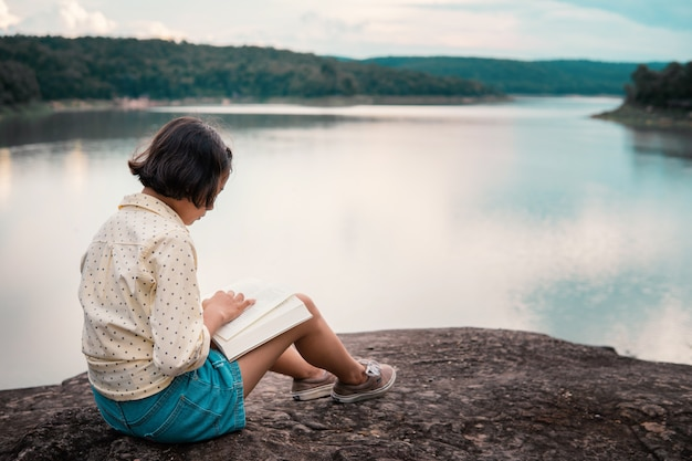 Chica asiática leyendo un libro junto al lago