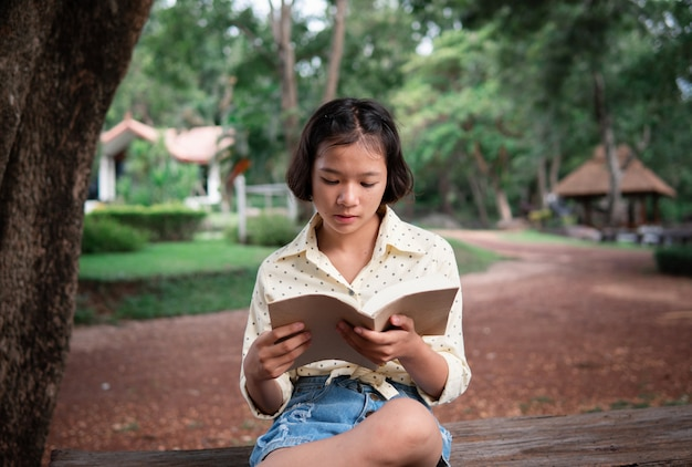 Chica asiática leyendo un libro en el parque