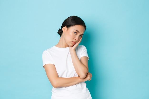 Chica asiática linda enojada y aburrida enfurruñada, apoyada en la palma y mirando con indiferencia, actuando no preocupada pero frunciendo el ceño enojada u ofendida, de pie fondo azul disgustado.