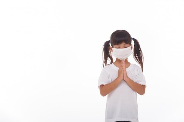 Chica asiática con máscara orando