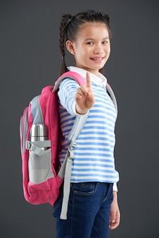 Chica asiática con mochila de pie y mostrando un dedo índice a la cámara