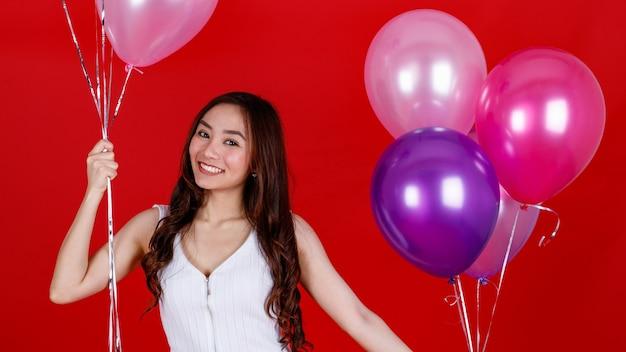 Chica asiática de pelo largo oscuro lindo y hermoso sosteniendo y jugando con globos de aire de colores con una sonrisa divertida y feliz sobre fondo rojo, tiro de luz de estudio.
