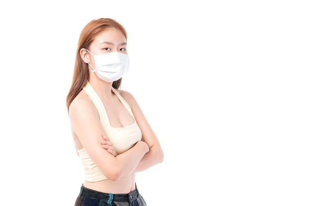Chica asiática de pie con los brazos cruzados con mascarilla protectora para protección durante el brote de cuarentena coronavirus covid19 sobre fondo blanco, proteger la propagación covid-19