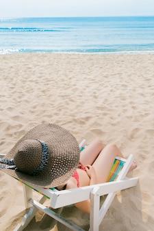 Chica asiática en la playa, ella se sienta en una silla de playa y se relaja.