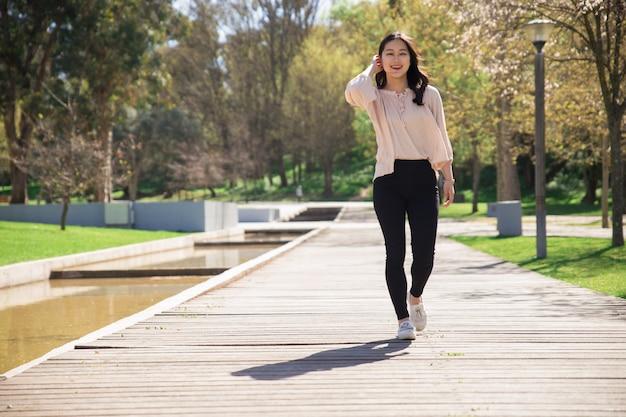 Chica asiática positiva en su camino a través del parque de la ciudad