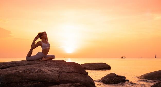 Chica asiática practica yoga en la playa amanecer mañana día