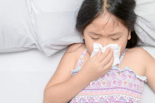 Chica asiática que sopla la nariz por el tejido