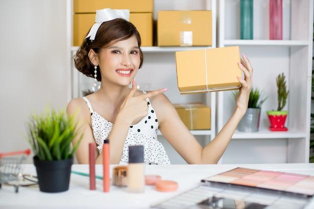 Chica asiática que trabaja en la oficina en casa y que clasifica el buzón de paquetería al servicio de entrega al cliente
