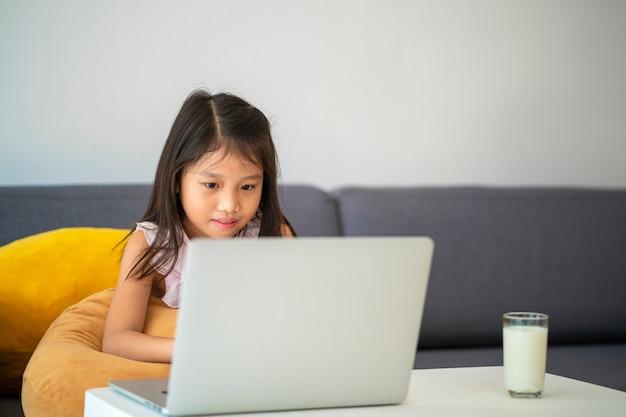 Chica asiática que usa la computadora de escritorio para estudiar en línea la educación en el hogar durante la cuarentena en casa educación en el hogar, estudio en línea, cuarentena en el hogar, aprendizaje en línea, virus corona o concepto de tecnología educativa