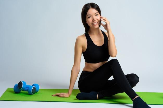 Chica asiática sentada y hablando por teléfono.
