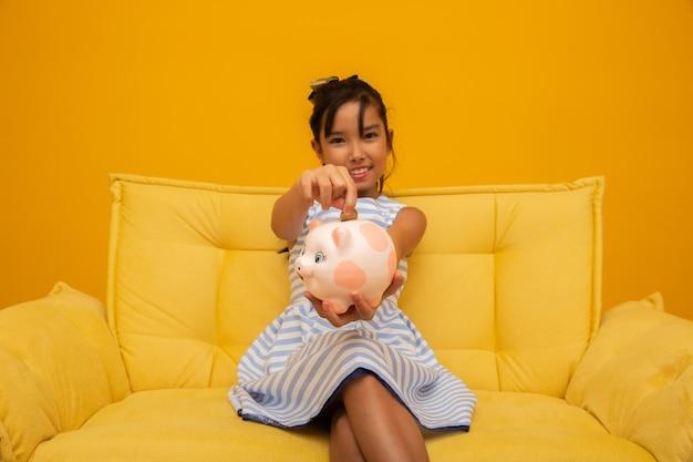 Chica asiática en el sofá con un banco de monedas de cerdo rosa