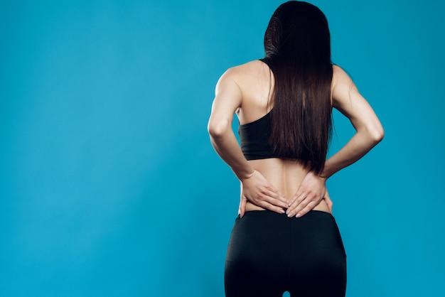 Chica asiática está sufriendo el esguince de espalda.