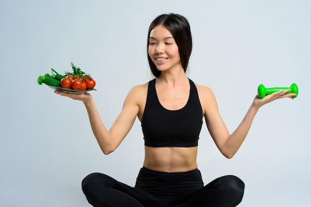 Chica asiática tiene pesas y plato de verduras.