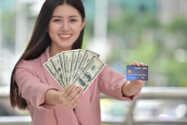Chica asiática en traje rosa envía una dulce sonrisa a una mano sosteniendo una tarjeta de crédito.