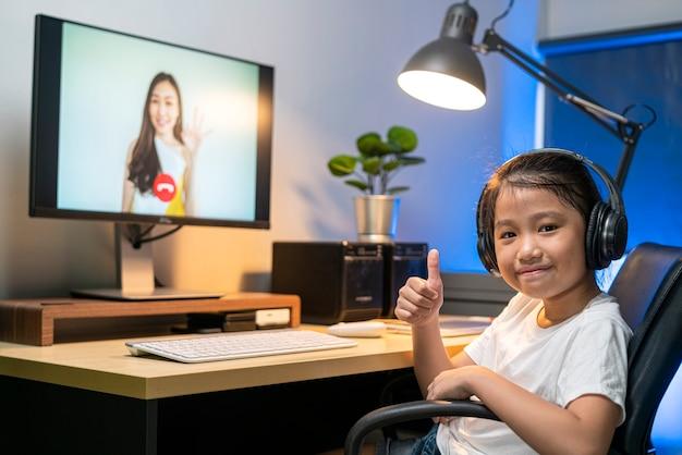Chica asiática con video teleconferencia para estudiar en línea con su maestra en casa