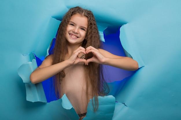 Chica asomando por un agujero en papel azul