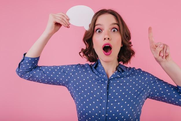 Chica asombrada divertida tiene una idea. modelo femenino de pelo corto entusiasta pensando en algo en la pared rosa.