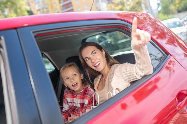 Chica asombrada mirando por la ventana en el asiento trasero del coche con su mamá apuntando hacia arriba