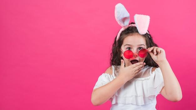 Chica asombrada en orejas de conejo