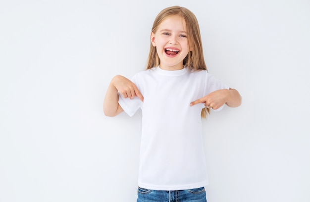 Chica de aspecto divertido con una camiseta en blanco entera apuntando a sí misma