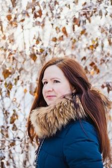 Chica de aspecto europeo en un paseo por el bosque de invierno, parque, invierno y nieve, salud, ropa de invierno, chaqueta