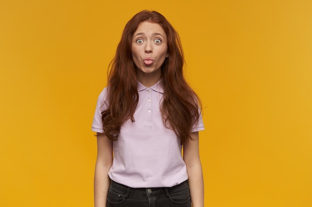 Chica de aspecto feliz, mujer pelirroja divertida con el pelo largo. vistiendo camiseta rosa. concepto de personas y emociones. mostrando una lengua. de humor juguetón. aislado sobre pared naranja